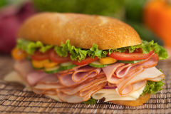 Turkey & ham sub with fresh veggies. Huge submarine sandwich with turkey, ham & cheese, topped with lettuce, tomatoes, cucumbers Stock Photography