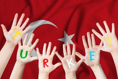Turkey inscription on the children`s hands against the background of a waving flag of the Turkey.  royalty free stock images