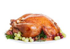 Turkey. A large a stuffed turkey on a platter garnished with grapes