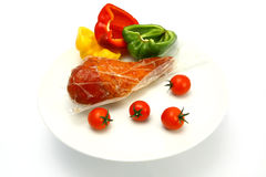 Turkey leg inside vacuum pack with tomatoes and pe Stock Images
