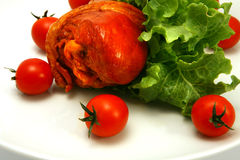 Turkey leg served with tomatoes and lettuce close Royalty Free Stock Images