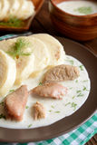Turkey meat with dill sauce and bread dumpling. A plate of turkey meat with dill sauce and bread dumpling on a wooden background stock photography