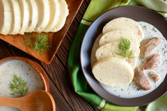 Turkey meat with dill sauce and bread dumpling. A plate of turkey meat with dill sauce and bread dumpling on a wooden background royalty free stock photos