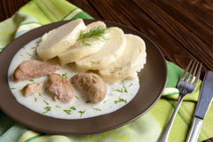Turkey meat with dill sauce and bread dumpling. A plate of turkey meat with dill sauce and bread dumpling on a wooden background royalty free stock photo