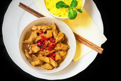 Turkey meat with red pepper, turmeric rice, chopstick, on black. Royalty Free Stock Photo
