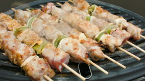 Turkey meat on sticks flips on a grill. Turkey meat with vegetables on wooden sticks fried on a grill stock footage