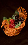 Turkey Reed Basket Filled with Grapes. Isolated on a Black Background. Focus is on the turkey's head Stock Images