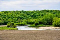 Turkey River Near A Plowed Field. The Turkey river running along side of a plowed field in Northeast Iowa Stock Photo