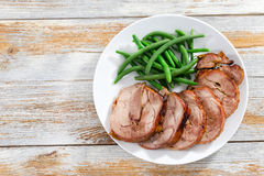 Turkey roulade cut in slices with boiled green beans Royalty Free Stock Photos