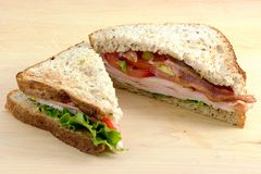 Turkey sandwich. With lettuce,tomatoes,bacon and avocado on cutting board Royalty Free Stock Photos