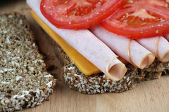 Turkey sandwich closeup. Closeup of turkey sandwich, on sesame bread, with tomatoes and cheese Royalty Free Stock Photos