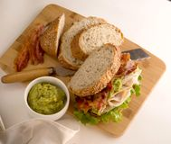 Turkey sandwich on a cutting board with ingredients on a white background stock images