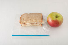 Turkey sandwich in a plastic bag with apple. Turkey sandwich with cheese in a plastic bag with apple  on white background Royalty Free Stock Photos