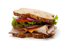 A turkey sandwich on whole-grain bread. A turkey sandwich on a whole-grain bread with lettuce, cheese and tomatoes on a white background stock images