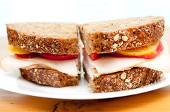 Turkey sandwich on whole wheat. Sliced smoked turkey breast with heirloom tomatoes on fresh and healthy organic seed bread Royalty Free Stock Photo