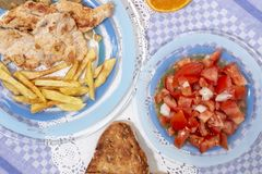 Turkey steak with french fries and tomato salad stock images