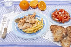 Turkey steak with french fries and tomato salad royalty free stock photography