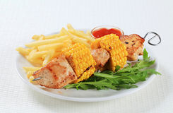 Turkey and sweetcorn skewer with French fries Royalty Free Stock Images