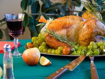 Turkey on table. Garnished turkey on green table with red wine Stock Image