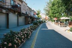 Turkiet Cappadocia, Goreme, Juni 12, 2017: Solig morgon i Goreme - gatan med blommor och stängt shoppar och tömmer Fotografering för Bildbyråer