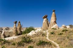Turkiet Cappadocia Pelare av att rida ut (stenen plocka svamp, buttes), runt om Cavusin Royaltyfria Foton