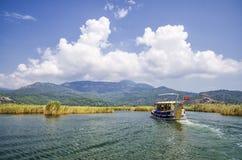 TURKIET DALYAN, MUGLA - JULI 19, 2016 nöjefartyg med turister i munnen av den Dalyan floden under Lycian gravvalv Arkivbild