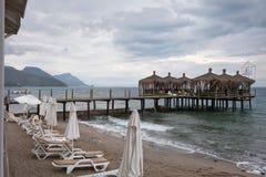 Turkiet ett hotell för semesterortstad Strand med solsängar och en pir molnig stormig havssky Royaltyfri Fotografi