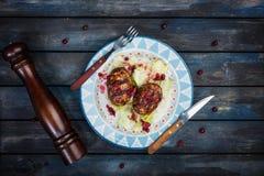 Turkiet kotletter med en ny bärsaucea- och isbergsallad tjänade som med bestick- och pepparmolar arkivfoto