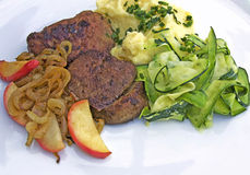 Turkiet lever med lökar, äppleskivor, potatisar och zucchinin Arkivfoto
