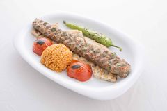 Turkish Adana Kebab served in plate. Turkish Adana kebab in plate with tomato,pepper,pide and bulgur in the oven stock photos