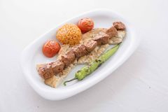 Turkish Adana Kebab served in plate. Turkish Adana kebab in plate with tomato,pepper,pide and bulgur in the oven royalty free stock photo