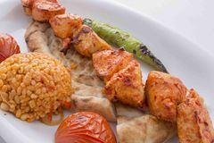 Turkish Adana Kebab served in plate. Turkish Adana kebab in plate with tomato,pepper,pide and bulgur in the oven stock photography