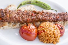 Turkish Adana Kebab served in plate. With tomato and pepper stock images