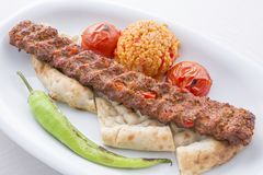 Turkish Adana Kebab served in plate. With tomato and pepper royalty free stock photos