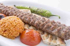 Turkish Adana Kebab served in plate. Turkish Adana kebab in plate with tomatos,peppers,pide and bulgur with barbecued royalty free stock photography