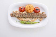 Turkish Adana Kebab served in plate. Turkish Adana Kebab in plate with tomatos,peppers,pide and bulgur with barbecued royalty free stock images