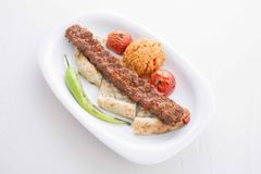 Turkish Adana Kebab served in plate. With tomato and pepper stock photography