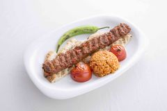 Turkish Adana Kebab served in plate. With tomato and pepper stock image