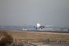 Turkish Airlines jet airliner approach to land at Madrid airport runway, seen from behind Royalty Free Stock Photos