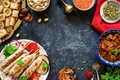 Turkish or arabic cuisine. Turkish food on dark stone background. Top view with copy space for text. Kebab, baklava, imam bayildi, spices and nuts Stock Image