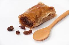 Turkish baklava with raisins and wooden spoon on white backgroun Royalty Free Stock Photo