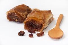Turkish baklava with raisins and wooden spoon on white backgroun Stock Image