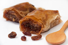Turkish baklava with raisins and wooden spoon on white backgroun Stock Images
