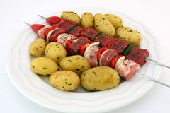 Turkish beef, lamb, and pork kebabs with potato on skewers. Turkish kebabs with beef, lamb, pork, onion, red and green peppers, with spicy herb potatoes on Royalty Free Stock Photo