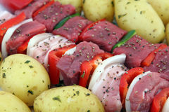Turkish beef, lamb, and pork kebabs with potato on skewers. Turkish kebabs with beef, lamb, pork, onion, red and green peppers, with spicy herb potatoes on Stock Photo
