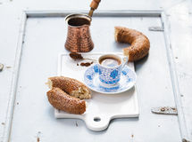 Turkish black coffee served in traditional ceramic cup with pattern, sesame bagel called simit on white serving board Stock Photos