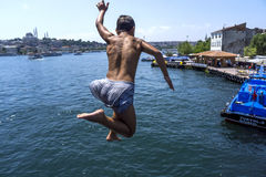 A Turkish boy jumps from Galata Bridge into Golden Horn in Istanbul in Turkey. Royalty Free Stock Images