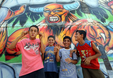 Turkish boys pose in front of a colourful mural at the Mersin amusement park in Turkey. Stock Image