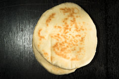 Turkish bread Bazlama on a black wooden table or board. Selectiv Stock Photography