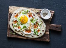 Turkish breakfast - flatbread with fried egg, yogurt, chili sauce and cheese on wooden chopping board, on dark background. Top view royalty free stock photography